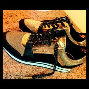 Michael Kors gold and black sneakers.
